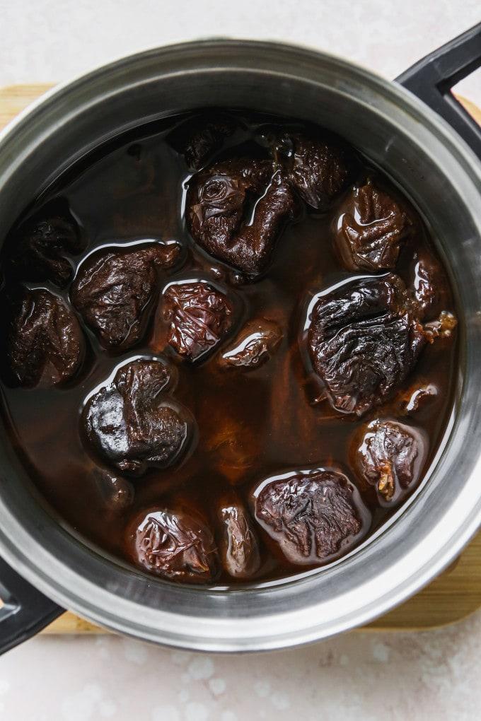 Overhead photo of stewed prunes in a saucepan.