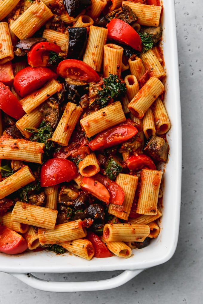 Overhead photo of pasta and veggies tossed in tomato sauce in a baking dish.