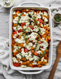 Overhead photo of an eggplant, zucchini, and tomato baked pasta topped with ricotta, parmesan and thyme in a baking dish.